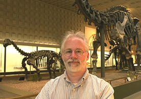 Portarit of Michael J. Donoghue. He stands, cross-armed, in front of huge dinosour skeletons from the main exhibition of the Peabody Museum.