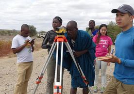 Six people stand doind different activities. One of them looks through the eye-piece of equipment mounted on a tripod. Behind them, clear skies can be seen.