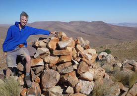 A middled aged man stands in a landscape with reddish mountains in the distance and a blue sky devoid of clouds. He is touching the tip of a pile of rocks next to him, so tall they reach up to his shoulder. He is wearing shorts, hiking boots, and a blue sweater. All his clothing is dusty and his hair is in disarray. He smiles.