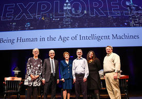 """Portrait of Catharine Bond Hill, President Peter Salovey, Margaret Warner, Shelly Kagan, Laurie Santos, and Brian Scassellati. They stand on a stage and behind a collosal sign reads """"Explores. Being Human in the Age of Intelligent Machines."""""""