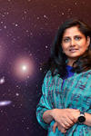 Portrait of Priyamvada Natarajan with a picture of the galaxy as background.