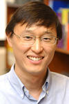 Formal portrait of Charles Ahn, standing in front of a bookshelf.
