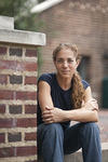 Portrait of Deborah Thomas, sitting by a brick wall, smiling.