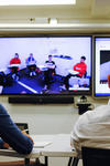 Kunsang Dorjee and Andy Archer sit in front a TV where they watch a class in real time happening in Columbia University.
