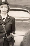 Photograph of Grace Hopper, who is standing in front of a car and dressed in uniform. The photo (and the car) seem to be from many decades ago.