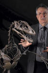Jacques Gauthier standing in front of a dinosour skeleton.