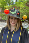 Portrait of Katie Melbourne, wearing her academic robes and a hat which contains planets and moons atop.