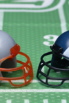 Two football helmets, facing each other, on a green numerated field. One shows the Patriot's logo, the other that of the Ram's.