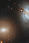 Colored image of space showing two bright, circular elements surrounded by other smaller, scatered ones.