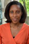 Portrait of Ebonya Washington, smiling, on a orange blouse.