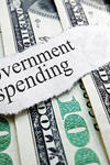 """Image of fanned one hundred dollar bills with a torn piece of paper on top of them reading """"Government spending"""""""