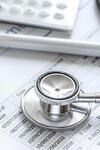 Image of medical bills and a stethoscope